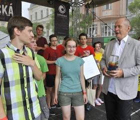 Vítězný tým zelených z Wichterlova gymnázia přebírá pohár z rukou rektora OU